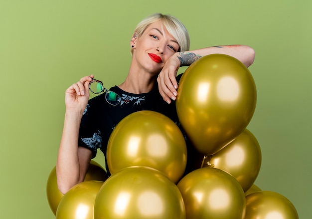 Pleased young blonde party girl standing behind balloons holding glasses putting arm on balloon looking at camera isolated on olive green background