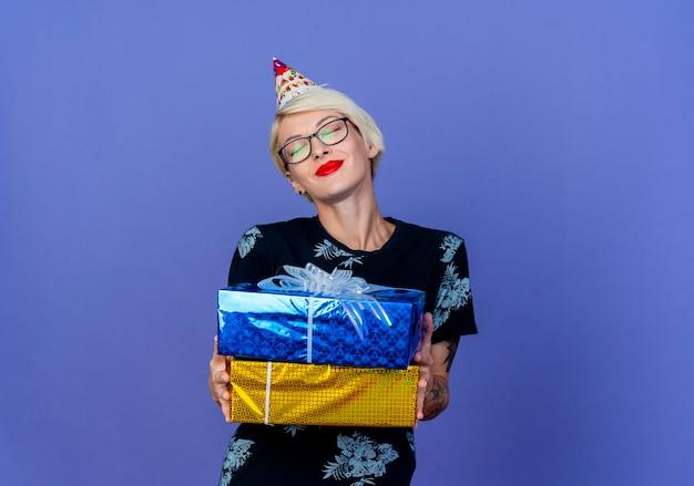 Довольная молодая блондинка тусовщица в очках и кепке дня рождения держит подарочные коробки с закрытыми глазами, изолированными на фиолетовом фоне с копией пространства