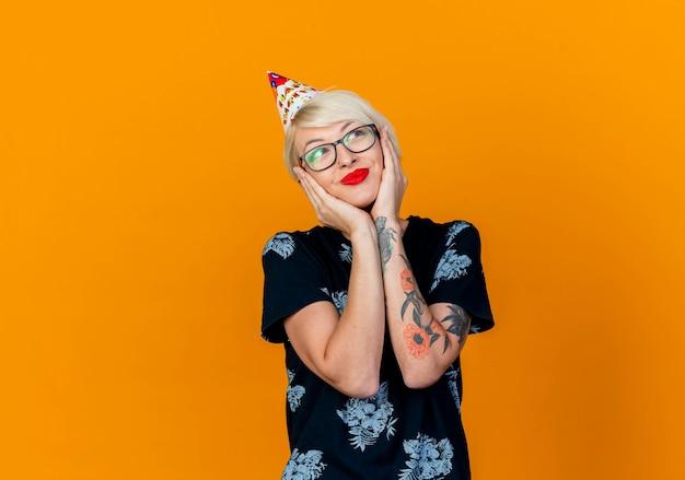 복사 공간 오렌지 배경에 고립 된 얼굴에 손을 유지 측면에서 찾고 안경과 생일 모자를 쓰고 기쁘게 젊은 금발 파티 소녀