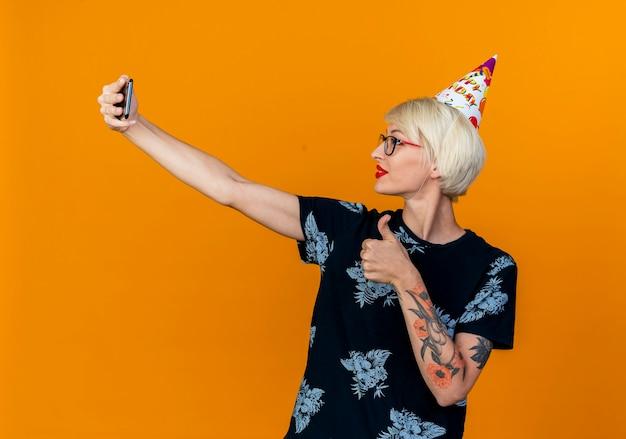 眼鏡と誕生日の帽子を身に着けている若いブロンドのパーティーの女の子がオレンジ色の背景で隔離の親指を見せて自分撮りを撮って喜んで