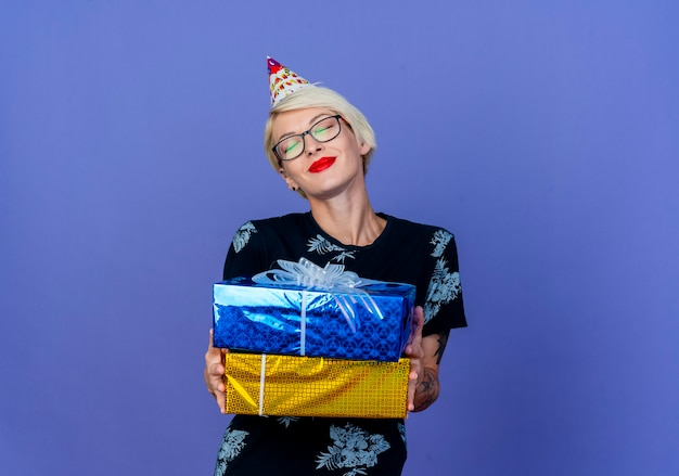 Pleased young blonde party girl wearing glasses and birthday cap holding gift boxes with closed eyes isolated on purple background with copy space