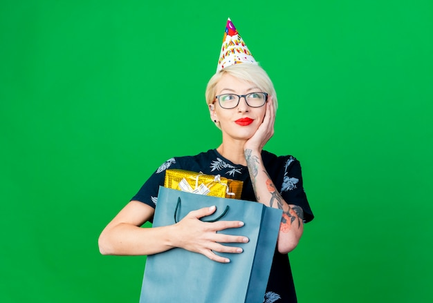 Lieta giovane ragazza bionda festa con gli occhiali e cappello di compleanno che tiene il sacchetto di carta con scatole regalo tenendo la mano sul viso guardando il lato sognando isolato su sfondo verde con spazio di copia