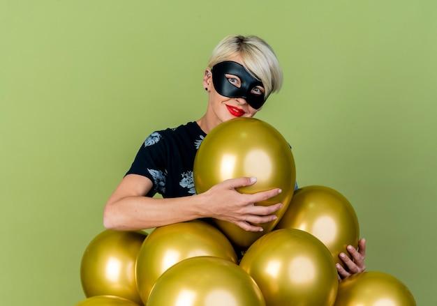 Lieta giovane ragazza bionda party indossando la maschera di travestimento in piedi dietro palloncini afferrandoli guardando la telecamera isolata su sfondo verde oliva