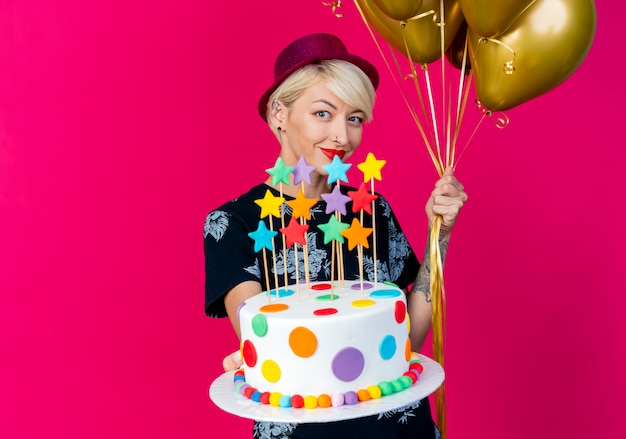 Lieta giovane ragazza bionda festa indossando il cappello del partito che guarda l'obbiettivo che tiene palloncini e allungando la torta di compleanno con le stelle verso la telecamera isolata su sfondo cremisi con lo spazio della copia