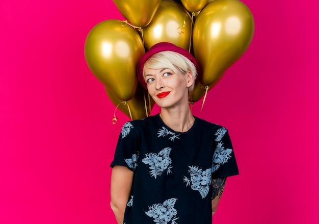 행복 한 젊은 금발 파티 소녀 복사 공간이 진홍색 배경에 고립 된 뒤에 손을 유지하는 측면을보고 풍선 앞에 서있는 파티 모자를 쓰고