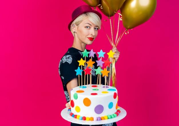 행복 한 젊은 금발의 파티 소녀 풍선을 들고 프로필보기에 서서 복사 공간이 진홍색 배경에 고립 된 카메라를 향해 별 생일 케이크를 뻗어 파티 모자를 쓰고