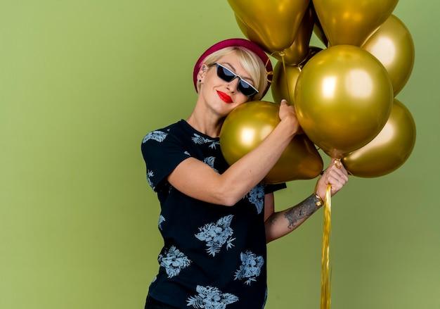 Lieta giovane ragazza bionda festa indossando cappello da festa e occhiali da sole in possesso di palloncini toccando il viso con uno di loro isolato su sfondo verde oliva con spazio di copia