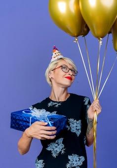 紫色の壁に隔離された夢に飛び込んで見上げる風船とギフトボックスを保持している眼鏡と誕生日の帽子を身に着けている若いブロンドのパーティーの女性を喜ばせる
