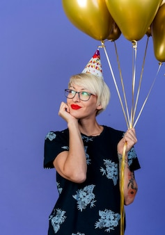 紫の壁に隔離された側を夢見てあごの下に手を置いて風船を保持している眼鏡と誕生日の帽子を身に着けている若いブロンドのパーティーの女性を喜ばせる