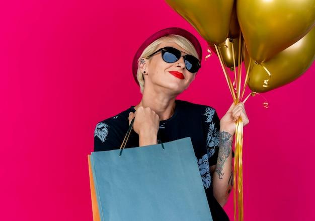 Довольная молодая блондинка вечеринка в шляпе и солнцезащитных очках держит воздушные шары и бумажные пакеты, изолированные на розовой стене с копией пространства