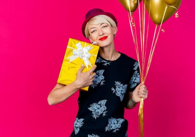 Довольная молодая светловолосая партийная женщина в партийной шляпе, держащая подарочную коробку и воздушные шары, смотрящую вперед, изолированную на розовой стене с копией пространства