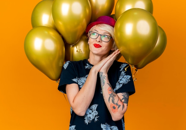 Pleased young blonde party woman wearing party hat standing in front of balloons keeping hands together looking at side pleading for something isolated on orange wall