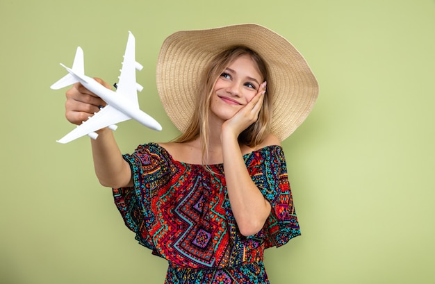 Pleased young blonde slavic girl with sun hat putting hand on her face and holding plane model