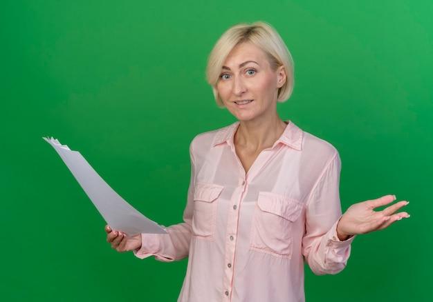 Lieta giovane bionda donna slava in possesso di documenti e mostrando la mano vuota isolata su sfondo verde