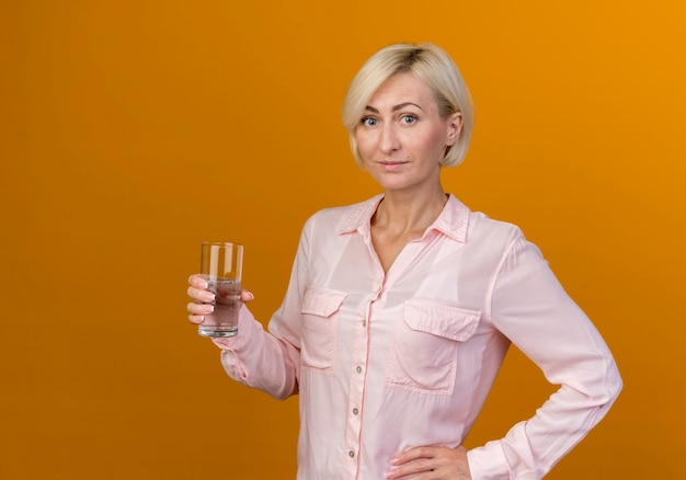 コップ一杯の水を保持し、腰に手を置く若い金髪のスラブ女性を喜ばせる