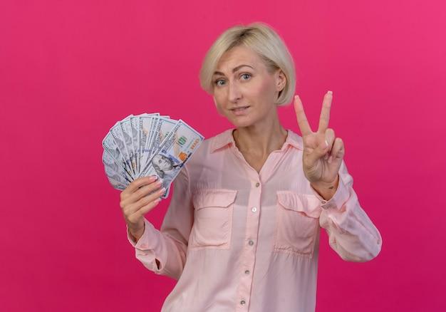 Lieta giovane bionda donna slava tenendo i soldi e facendo segno di pace isolato su sfondo rosa