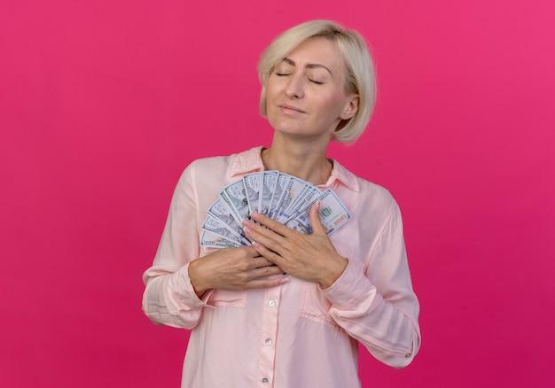 Lieta giovane bionda donna slava che tiene i soldi con gli occhi chiusi isolati su sfondo rosa con copia spazio