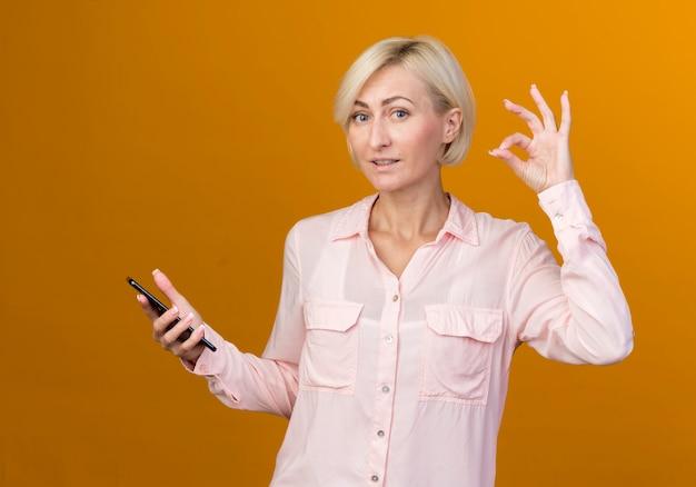 Lieta giovane bionda donna slava tenendo il telefono e mostrando okey gesto