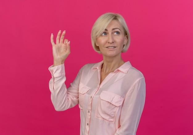 ピンクの背景に分離されたokサインをしている側を見て喜んで若い金髪のスラブ女性