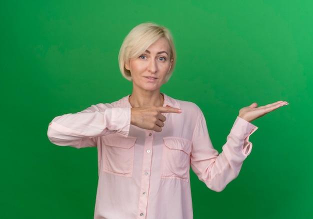 Lieta giovane bionda donna slava guardando la telecamera che mostra la mano vuota e puntando verso di essa isolato su sfondo verde