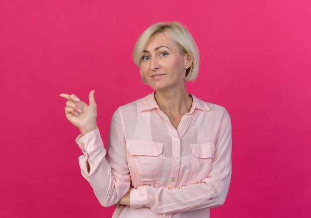 Довольная молодая блондинка славянская женщина, указывая на сторону, изолированную на розовом фоне с копией пространства