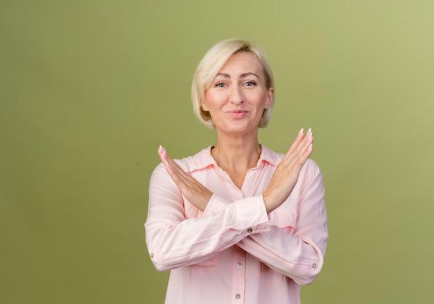 Lieta giovane donna slava bionda che mostra il gesto di non isolato sulla parete verde oliva