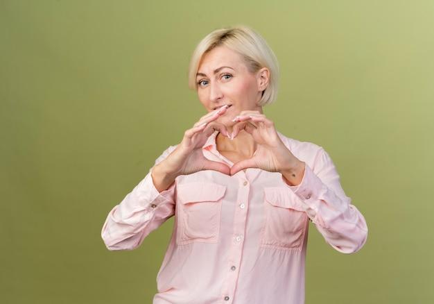 Felice giovane donna slava bionda che mostra il gesto del cuore