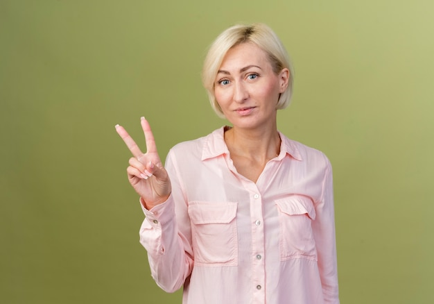 평화 제스처를 보여주는 기쁘게 젊은 금발 슬라브 여자