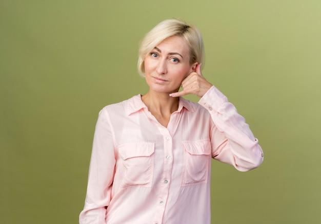 電話のジェスチャーを示す満足している若いブロンドのスラブ女性