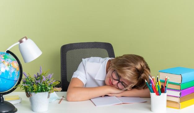目を閉じて机の上に頭を休んでいる学校の道具と机に座って眼鏡をかけている若いブロンドの学生の女の子を喜ばせる