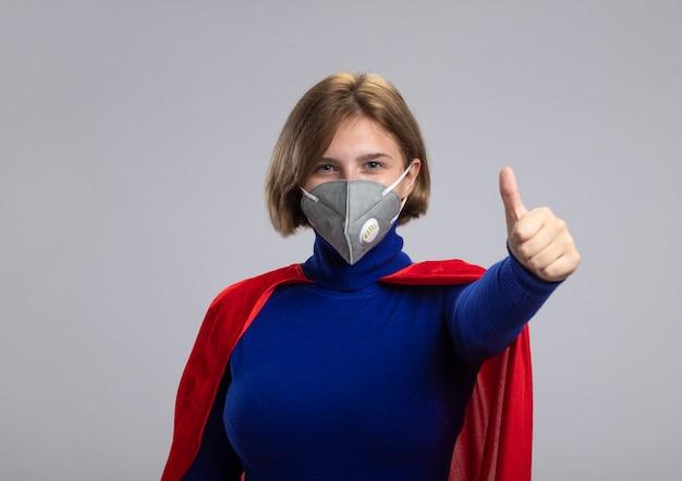 Довольная молодая блондинка супергерой в красной накидке в защитной маске смотрит в камеру, показывая большой палец вверх изолирован на белом фоне с копией пространства