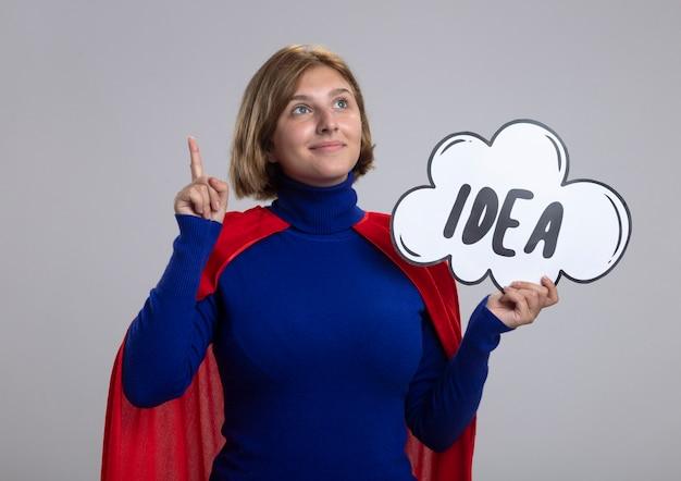 Lieta giovane ragazza bionda del supereroe in mantello rosso che tiene la bolla di idea alla ricerca e rivolta verso l'alto isolato su sfondo bianco