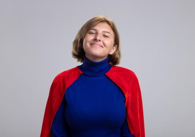 Lieta giovane ragazza bionda del supereroe in mantello rosso isolato sulla parete bianca con lo spazio della copia