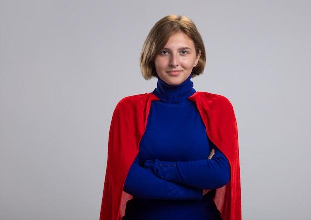 Lieta giovane ragazza bionda del supereroe in mantello rosso in piedi con la postura chiusa isolata sulla parete bianca con lo spazio della copia