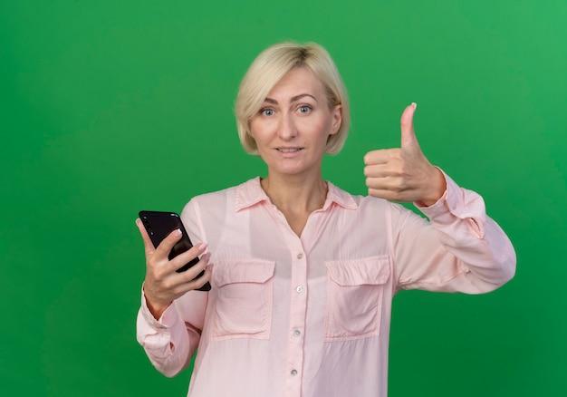 Довольная молодая блондинка женщина держит мобильный телефон и показывает палец вверх