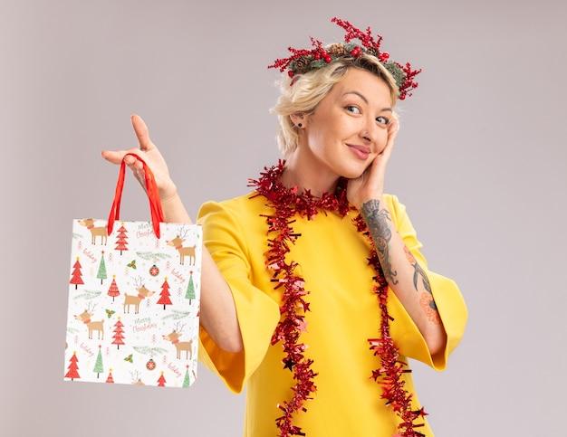 흰색 배경에 고립 된 얼굴을 만지고 카메라를보고 크리스마스 선물 가방을 들고 목에 크리스마스 머리 화 환과 반짝이 갈 랜드를 입고 기쁘게 젊은 금발의 여자