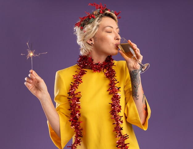 クリスマスのヘッドリースと見掛け倒しの花輪を首に身に着けている幸せな若いブロンドの女性は、休日の線香花火を保持し、紫色の背景で隔離の目を閉じてシャンパングラスを飲む