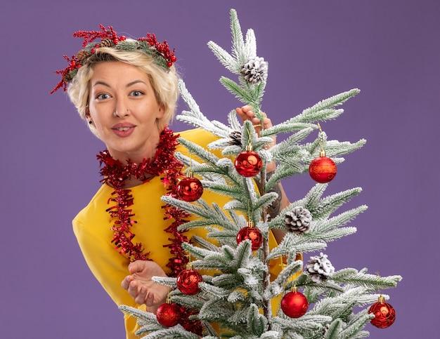 Довольная молодая блондинка в рождественском венке и гирлянде из мишуры на шее стоит за украшенной елкой и смотрит изолированно на фиолетовой стене