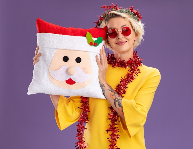 Pleased young blonde woman wearing christmas head wreath and tinsel garland around neck holding santa claus pillow with closed eyes isolated on purple wall