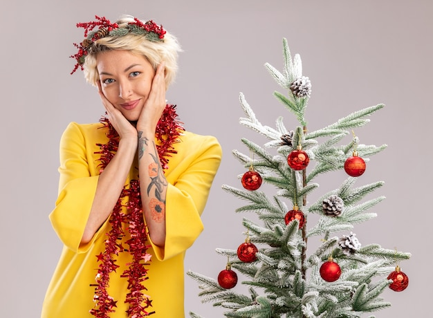 Lieta giovane donna bionda che indossa la testa di natale ghirlanda e orpello ghirlanda intorno al collo in piedi vicino all'albero di natale decorato tenendo le mani sul viso guardando la telecamera isolata su sfondo bianco
