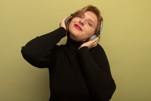 Pleased young blonde woman wearing and putting hands on headphones listening to music with closed eyes isolated on olive green wall with copy space