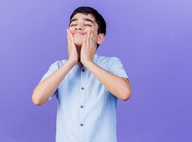 Довольный мальчик держит руки на лице с закрытыми глазами, изолированными на фиолетовой стене