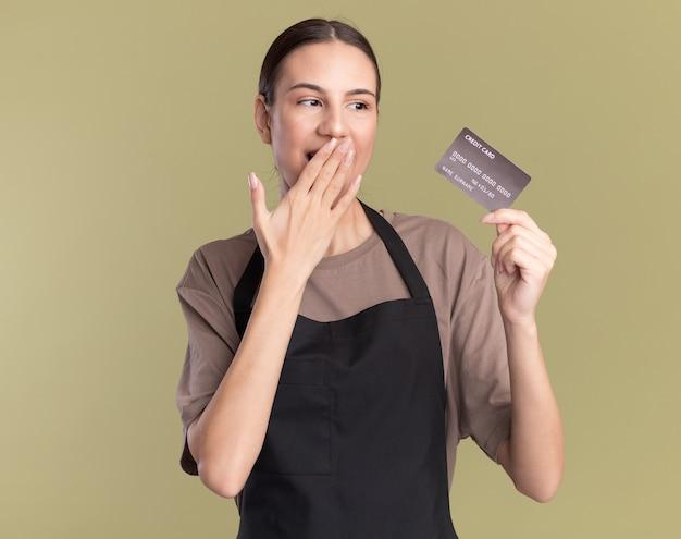 Довольная молодая брюнетка-парикмахер в униформе кладет руку на рот, держа и глядя на кредитную карту на оливково-зеленом