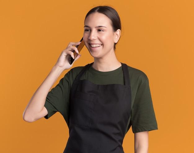 오렌지에 측면을보고 전화로 균일 한 회담에서 기쁘게 젊은 갈색 머리 이발소 소녀