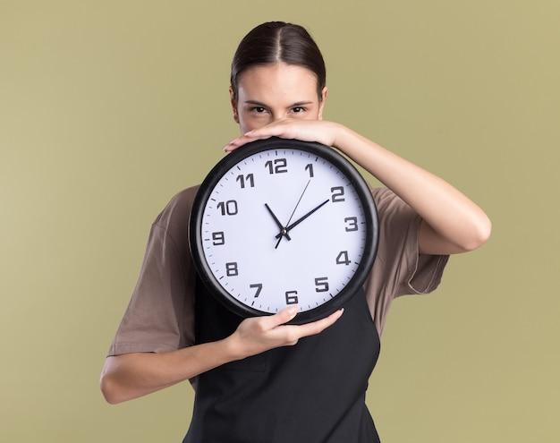 Lieta giovane ragazza bruna barbiere in uniforme tiene l'orologio su verde oliva