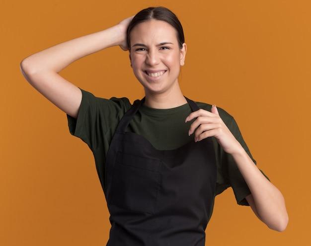 Lieta giovane ragazza bruna barbiere in uniforme mette la mano sulla testa dietro e guarda la telecamera sull'arancio