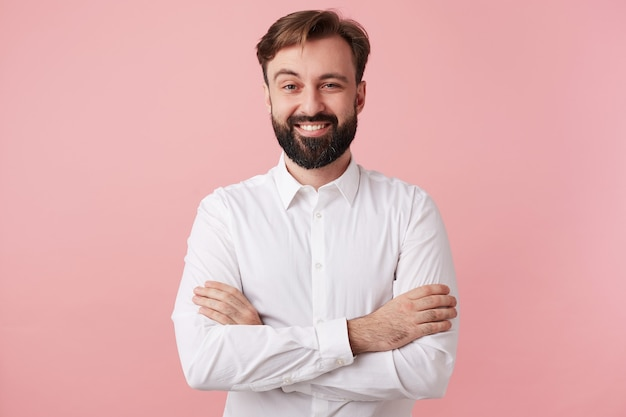 Pleased young brunette bearded man with short haircut keeping folded hands on his chest while looking cheerfully to front with raised eyebrow, isolated over pink wall