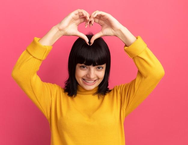 Lieta giovane ragazza caucasica bruna gesti segno di cuore sopra la testa