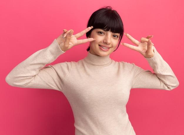 Felice giovane ragazza bruna caucasica gesti il segno di vittoria con due mani sul rosa
