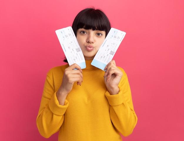 La giovane ragazza caucasica castana piacevole tiene i biglietti aerei isolati sulla parete rosa con lo spazio della copia